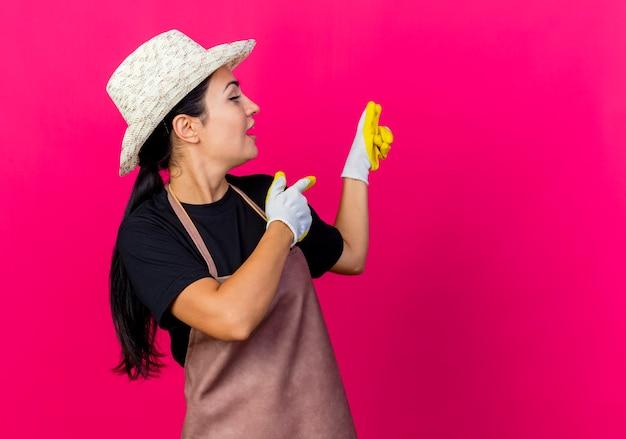 Młoda piękna kobieta ogrodnik w gumowych rękawiczkach, fartuchu i kapeluszu, wskazując palcami wskazującymi z powrotem, będąc zaskoczonym stojąc