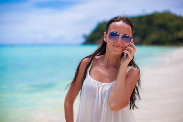 Młoda piękna kobieta opowiada na jej telefonie przy plażą
