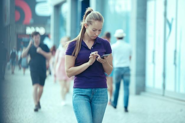 Młoda piękna kobieta opowiada na telefonie komórkowym plenerowym.