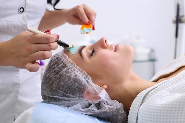 Młoda piękna kobieta otrzymujących maseczka na twarz z gliny w salonie kosmetycznym spa