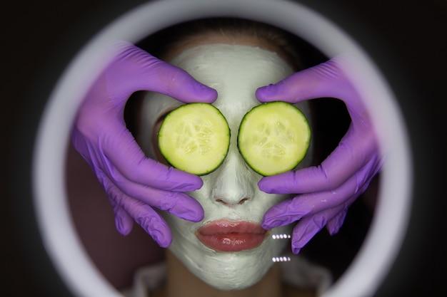 Młoda piękna kobieta otrzymuje glinianą maskę do twarzy z ogórkiem na oczy w salonie piękności spa.