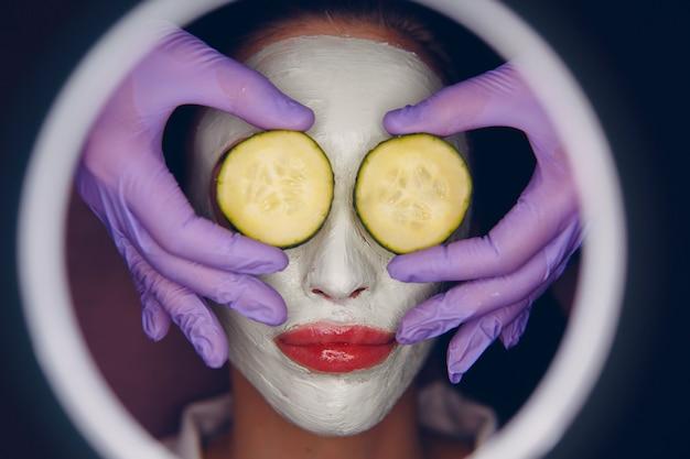 Młoda piękna kobieta otrzymuje maseczkę glinianą do twarzy z ogórkiem na oczy w salonie piękności spa z lupą.