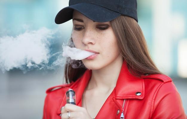 Młoda piękna kobieta pali papierosa z dymem (vaping)