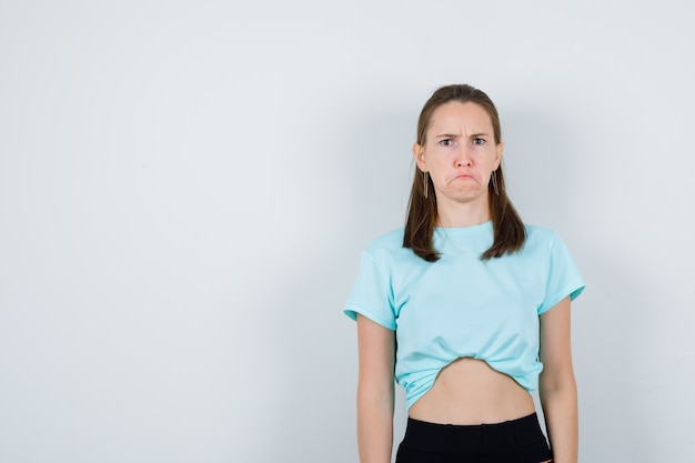 Młoda piękna kobieta patrząc na kamery w t-shirt i patrząc w złym humorze, widok z przodu.