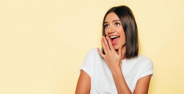 Młoda piękna kobieta patrzeje kamerę. modna dziewczyna w luźnych letnich białych t-shirtach i jeansowych szortach. pozytywna kobieta wykazuje emocje na twarzy. zszokowany i zaskoczony rękami w pobliżu twarzy