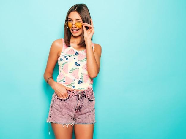 Młoda piękna kobieta patrzeje kamerę. modna dziewczyna w swobodnej letniej białej koszulce i jeansowych szortach w okrągłych okularach przeciwsłonecznych. pozytywna kobieta wykazuje emocje na twarzy. śmieszny model odizolowywający na błękicie