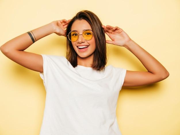 Młoda piękna kobieta patrzeje kamerę. modna dziewczyna w swobodnej letniej białej koszulce i jeansowych szortach w okrągłych okularach przeciwsłonecznych. pozytywna kobieta wykazuje emocje na twarzy. śmieszny model odizolowywający na kolorze żółtym
