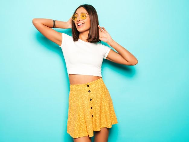 Młoda piękna kobieta patrzeje kamerę. modna dziewczyna w swobodnej letniej białej koszulce i żółtej spódnicy w okrągłych okularach przeciwsłonecznych. pozytywna kobieta wykazuje emocje na twarzy. śmieszny model odizolowywający na błękicie