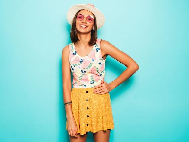 Młoda piękna kobieta patrzeje kamerę w kapeluszu. modna dziewczyna w swobodnej letniej białej koszulce i żółtej spódnicy w okrągłych okularach przeciwsłonecznych. pozytywna kobieta wykazuje emocje na twarzy. śmieszny model odizolowywający na błękicie
