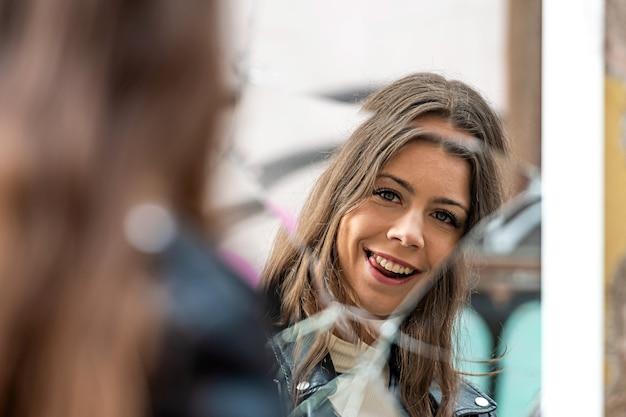 Młoda, piękna kobieta patrzy na swoje odbicie w zbitym lustrze