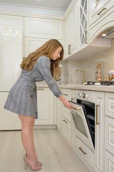 Młoda piękna kobieta piecze coś w piekarniku elektrycznym