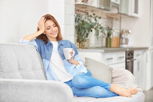 Młoda piękna kobieta pije herbatę w kuchni