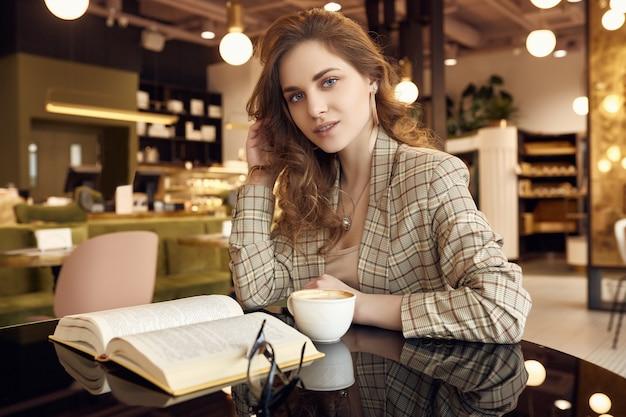 Młoda piękna kobieta pije kawę i czytelniczą książkę w kawiarni