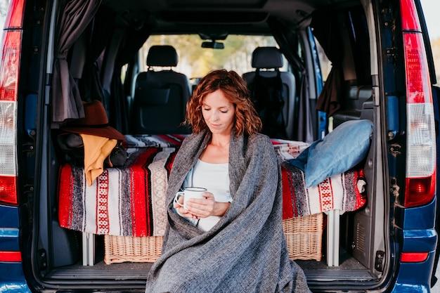 Młoda piękna kobieta pije kawę lub herbatę obozuje na zewnątrz z samochodem dostawczym. koncepcja podróży. widok z góry