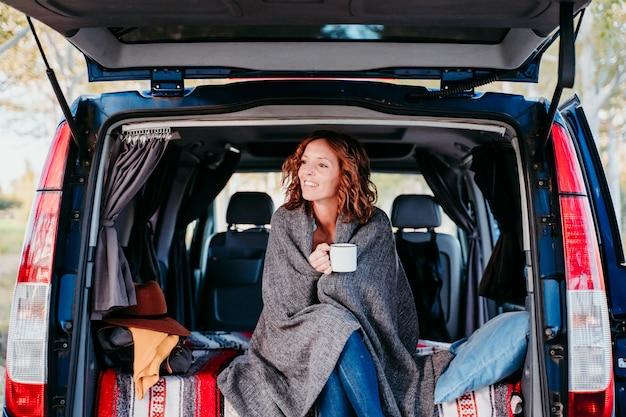 Młoda piękna kobieta pije kawę lub herbatę obozuje na zewnątrz z samochodem dostawczym. koncepcja podróży