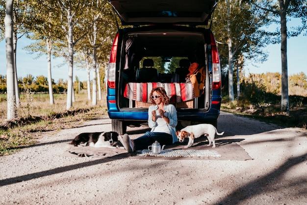 Młoda piękna kobieta pije kawę lub herbatę obozuje na zewnątrz z vanem i jej dwoma psami. koncepcja podróży