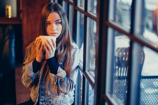 Młoda piękna kobieta pije kawę w barze