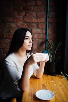 Młoda piękna kobieta pije kawę w kawiarni na świeżym powietrzu.