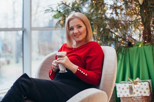 Młoda piękna kobieta pije kawę w pobliżu choinki