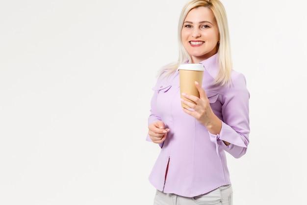 Młoda piękna kobieta pije papierową szklankę kawy na odosobnionym białym tle