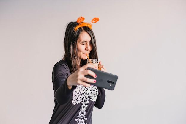 Młoda piękna kobieta pije sok pomarańczowego i bierze selfie z telefonem komórkowym. ubrany w czarno-biały kostium szkieletu. koncepcja halloween. wewnątrz
