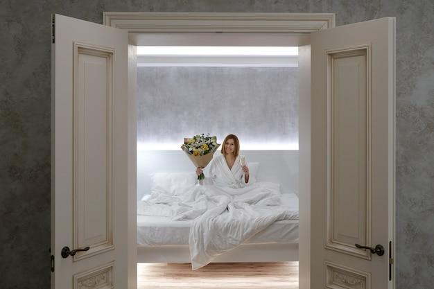 Młoda piękna kobieta pije szampana w łóżku. świętowanie urodzin w sypialni.