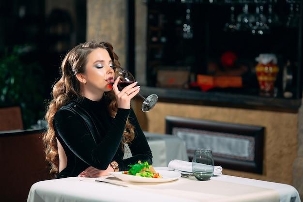 Młoda piękna kobieta pije wino w restauracji.