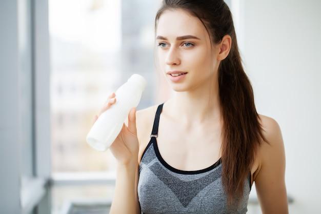 Młoda piękna kobieta pije z plastikowej butelki jogurtu
