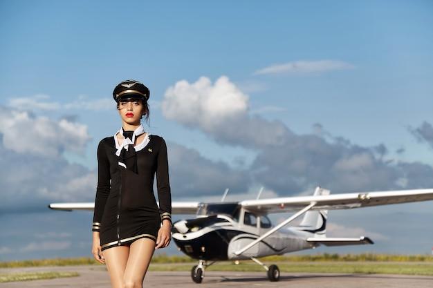 Młoda piękna kobieta pilot lub stewardesa przed samolotem.