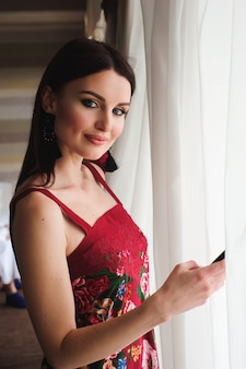 Młoda piękna kobieta pisze sms na swój telefon komórkowy.