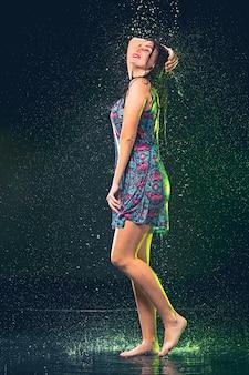 Młoda piękna kobieta pod pluśnięciem deszcz