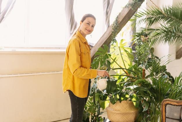 Młoda piękna kobieta podlewania kwiatów i roślin w ogrodzie domu