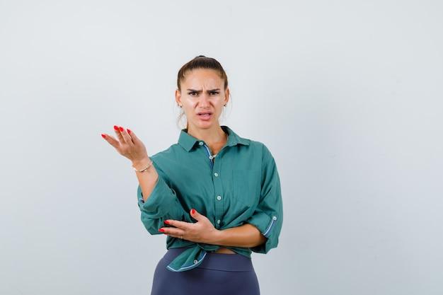 Młoda piękna kobieta podnosząc rękę w agresywny sposób w zielonej koszuli i patrząc wściekle, widok z przodu.