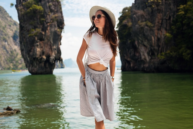 Młoda piękna kobieta podróżująca w tajlandii, wakacje, styl casual, okulary przeciwsłoneczne, kapelusz, bawełniana spódnica, t-shirt, uśmiechnięta, szczęśliwa, przygody