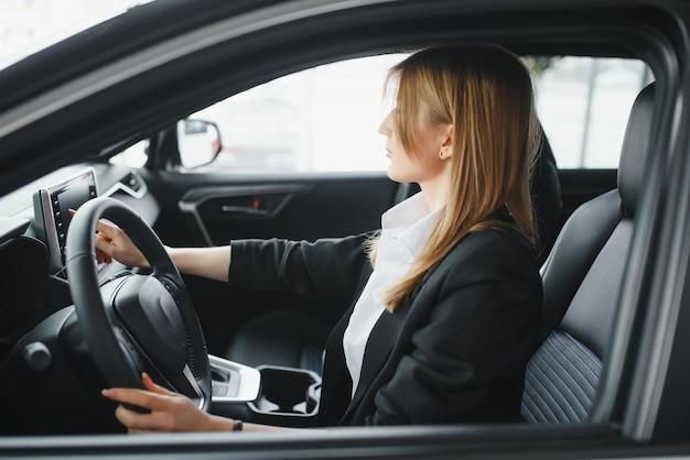 Młoda piękna kobieta, pokazując swoją miłość do samochodu w salonie samochodowym