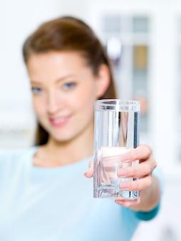 Młoda piękna kobieta pokazuje szklankę wody