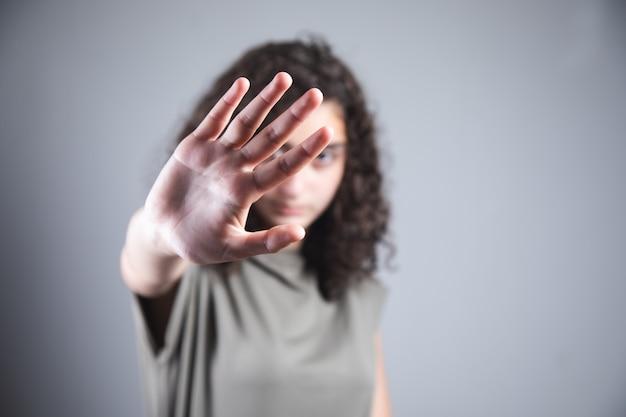 Młoda piękna kobieta pokazuje znak stop.
