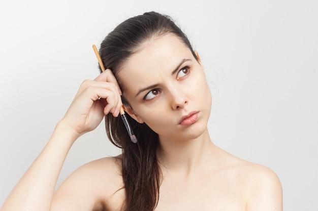 Młoda piękna kobieta portret makijaż pędzla zdziwiony wygląd