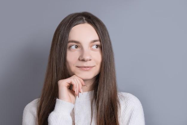 Młoda piękna kobieta portret z ciemnymi włosami na sobie biały sweter odwraca wzrok z lekkim uśmiechem. studio strzał na szarym tle. kopiowanie miejsca.