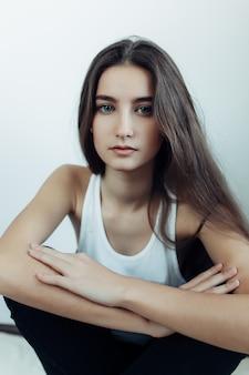 Młoda piękna kobieta pozuje na białej ścianie