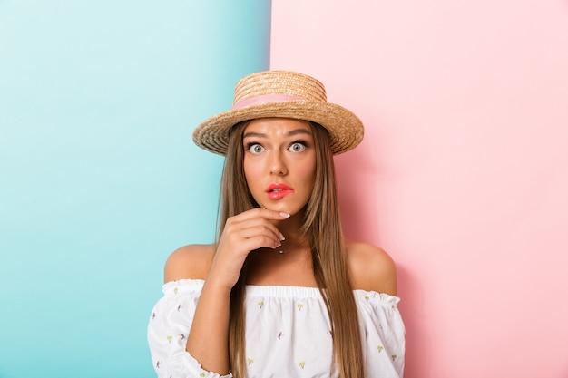 Młoda piękna kobieta pozuje na białym tle na sobie kapelusz.