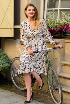 Młoda piękna kobieta pozuje obok roweru na ulicach starego miasta.