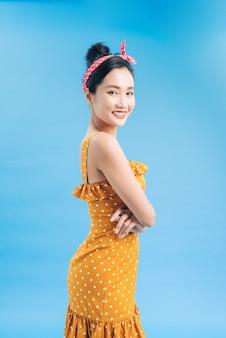Młoda piękna kobieta pozuje w nowej casualowej żółto-białej sukience w kropki na niebiesko