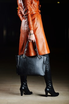 Młoda piękna kobieta pozuje z modnymi skór ubraniami