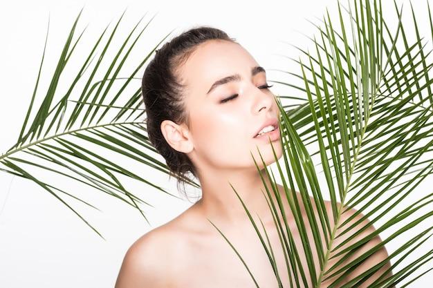 Młoda piękna kobieta pozuje z zielonymi palmowymi liśćmi