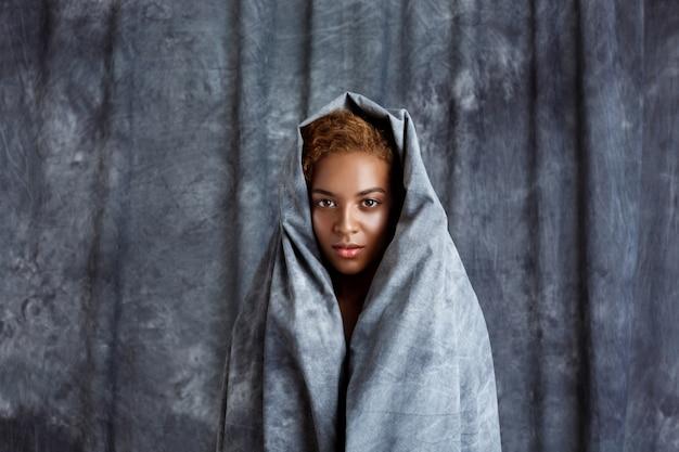 Młoda piękna kobieta pozuje, zawija w szarego płótno