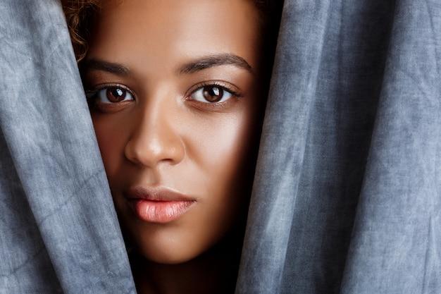 Młoda piękna kobieta pozuje, zawijając się w szare tkaniny