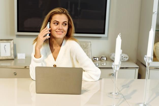 Młoda piękna kobieta pracuje na komputerze w domu z laptopem na białym biurku jako freelancer. młoda kobieta rozmawia przez telefon podczas pracy w domu.