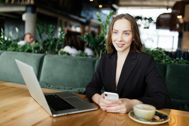 Młoda piękna kobieta pracuje na laptopie w kawiarni