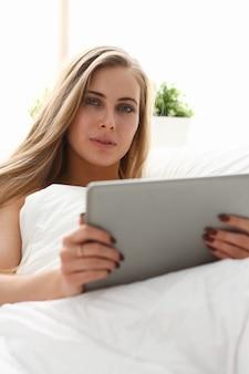 Młoda piękna kobieta pracuje z tabletem, pozostając w łóżku wcześnie rano